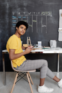 teen in yellow tee and checkered pants holds ipad in classroom