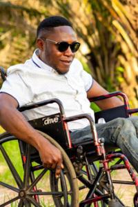 young adult in wheelchair and sunglasses crosses campus