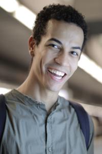 teen in gray shirt and backpack smiles at camera