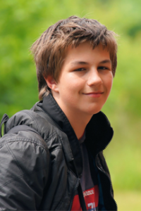 teen in black jacket with backpack smiles at camera