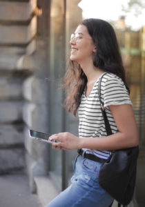 Young woman in striped shirt holds tablet